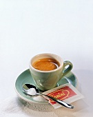Espresso in green cup; spoon; sugar and sugar packet