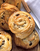 Snail rolls with raisins on wooden board, beside knife