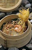 Scampi on pike-perch in bamboo steamer on stone background