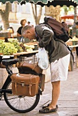 Man with bicycle at vegetable stall at market in Provence