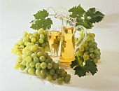 Grape juice in glass and jug surrounded by green grapes