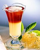 Elderflower and raspberry drink in glass; elderflowers