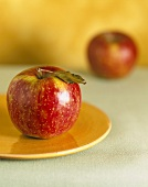 Red apple with leaf on yellow plate in front of second apple