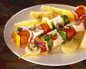 Vegetable and tofu kebab with fried potatoes on plate
