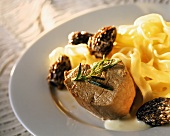 Fried veal steak with morels and ribbon pasta on plate