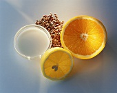 Orange and lemon halves, linseed and milk in bowl