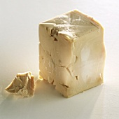 Cube of fresh yeast on light background
