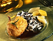 Braised guinea-fowl legs with wild rice and leeks on plate