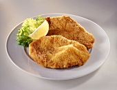 Two Wiener Schnitzel with lemon wedge on white plate