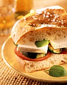 Flatbread sandwich of tomato, courgette and sheep's cheese