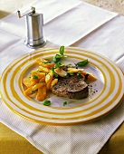 Peppered steak with carrots and fresh basil on plate