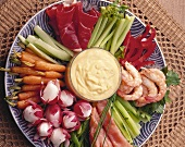 Plate of raw vegetables with shrimps, salmon, raw ham & dip