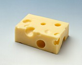 Emmental cheese (rectangular piece) on light background