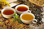 Three medicinal teas in cups with dried medicinal herbs
