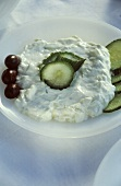 Tzaziki with sliced cucumber and olives on a white plate