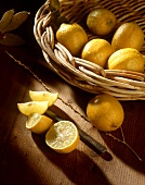 Lemons in a Basket with Sliced Lemons on Wood