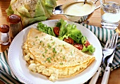 Omelette with cauliflower and salad on plate; Béchamel sauce