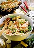 Rigatoni salad with salmon, leek and peanuts in a dish