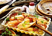 Scorzonera and tomato gratin with ham in baking dish