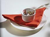 Leer gegessenes Souffle-Töpfchen mit Löffel auf Serviette