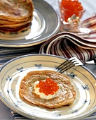 Russian blinis with sour cream and caviare on plate