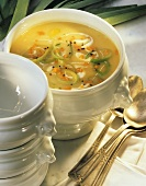 Potato and leek soup with diced carrots in soup tureen