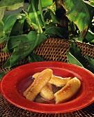 Flambierte Bananen in Honigsauce auf rotem Teller