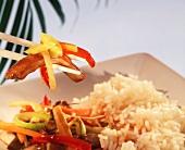 Chop suey with pork on chopsticks above plate