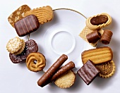 Various biscuits and chocolate rolls, grouped around plate