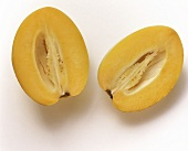 Two pepino melon halves on light background