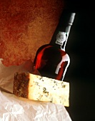 A Blue Cheese Wedge with a Bottle of Red Wine