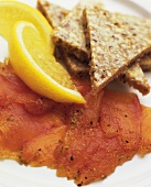 Raw Sliced Salmon with Bread Triangles and Lemon Wedges