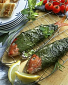 Red mullet in vine leaves on grill rack