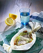 Cod with vegetables wrapped in greaseproof paper on glass plate