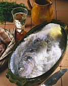Whole sea bass in salt crust; white wine glass; jug
