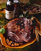 Wild boar with sweet chestnut on a platter; Red wine bottle