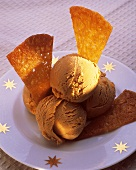 Caramel ice cream with caramelised wafers, on a plate