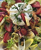 Salad leaves with goat's cheese and fruit (filling the picture)