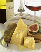 Cheddar with pear, fig and bread on a plate; red wine