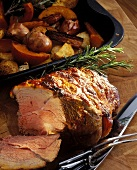 Roast leg of lamb, slices cut, by roasting dish with vegetables