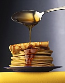 Maple Syrup Dripping from Spoon Onto Plate of Pancakes