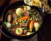 Beef stew with vegetables in cast-iron pan