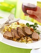 Sliced roast beef on couscous; hand with red wine glass