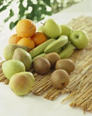 Kiwis, bananas, oranges, apples and pears on straw mat