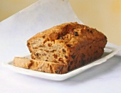 Fruit loaf with raisins, a slice cut, on white plate
