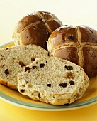 Hot cross buns, one halved, on plate
