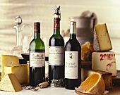 Various types of cheese and three red wine bottles