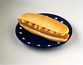 Hot dog with mustard on blue plate with white stars