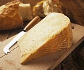 Pecorino auf Schneidebrett mit Käsemesser, dahinter Brot