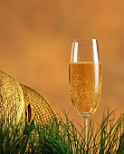 A champagne glass in the grass beside a straw hat